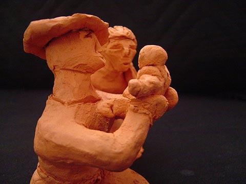 Pai e mãe olham felizes para seu novo bebêzinho. Pai segura neném no colo, mamãe ao lado. (Vista Lateral)