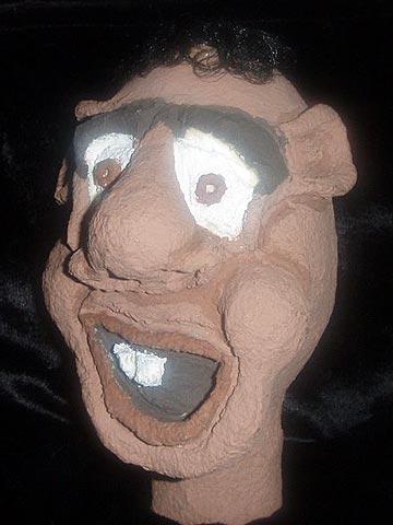 Cabeça de um boneco feio como um Jéca, feito em papél machê para um espetáculo de teatro infantil.