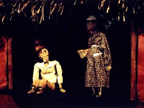 Bonecos de papel machê, um homem sentado e uma mulher em pé com uma cesta nos braços, são os pais de Nanã.