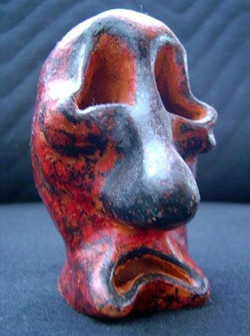 Escultura de cerâmica com a face da dor, pintada a giz de cera e envernizada.