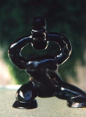 Escultura de um ser, sem pescoço, segurança sua cabeça já quase perdida, fora do corpo, a ponto de perdê-la.